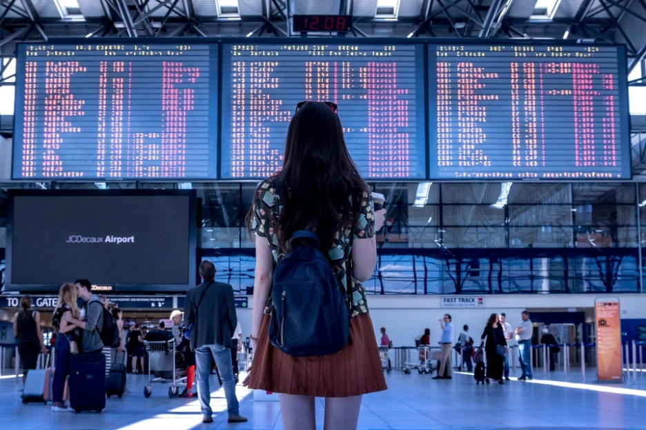 Woman gazing at airport departure board